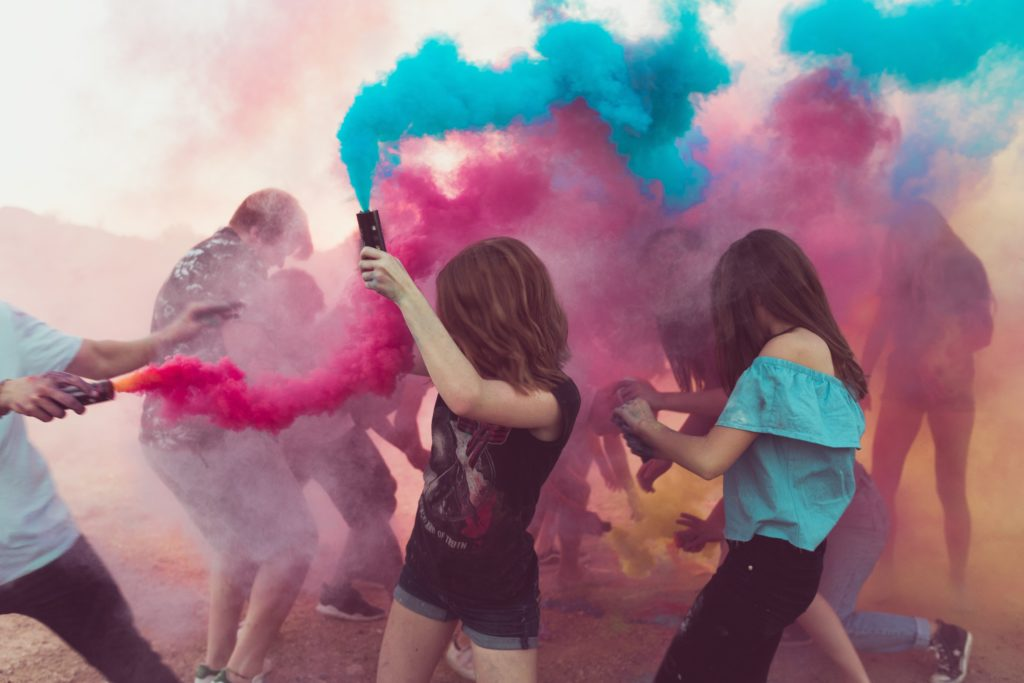 Middle school kids playing with pink and blue color powder.