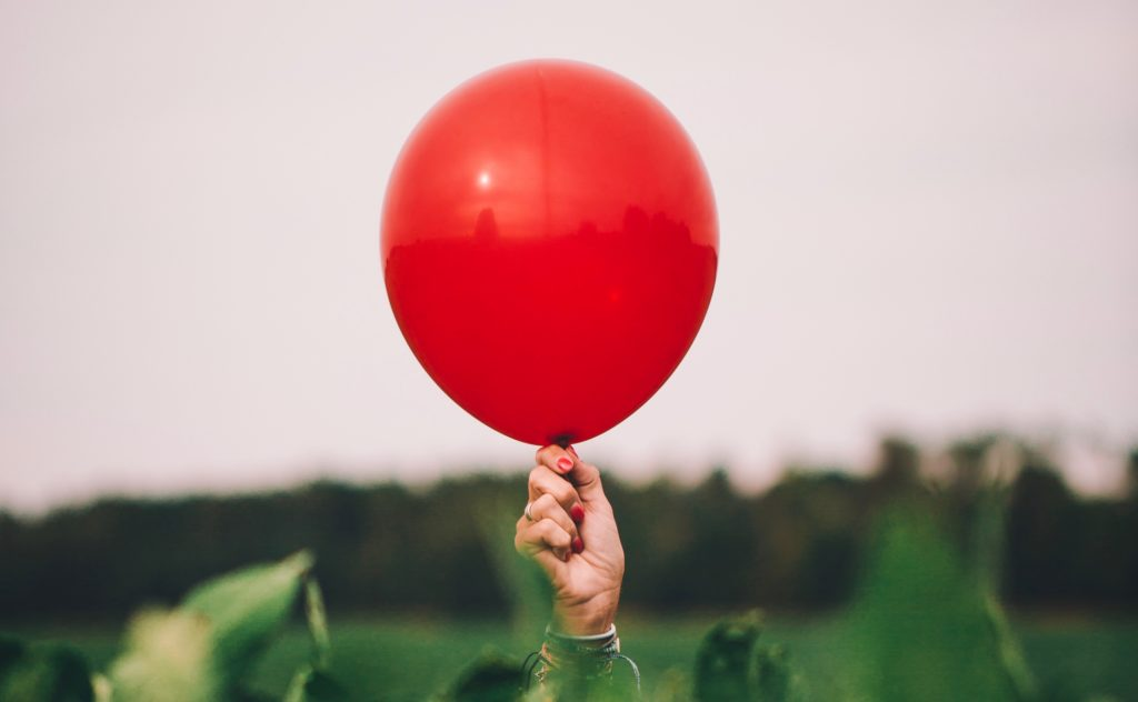 Woman holding single red balloon.