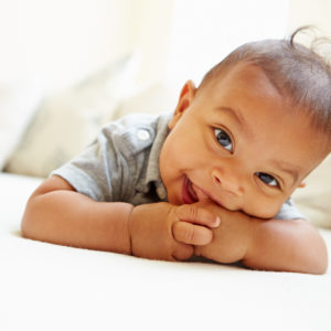 African American Baby smiling at camera to illustrate the Butterfly Academy's class on reproduction