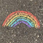 chalk drawing of a rainbow on the pavement, indicative of LGBTQIA issues