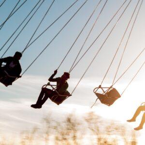 Image of teenagers on carnival swings.
