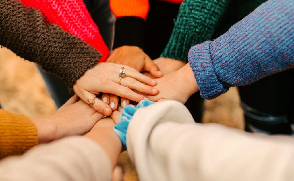 Image shows group of people in colorful sweaters all putting their hands in as a sign of unity